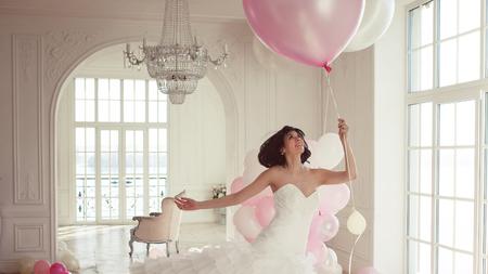 Jeune femme en robe de mariée dans un intérieur de luxe vole sur des ballons roses et blancs. Charmante jeune mariée brune avec une coupe courte dans des robes élégantes de Quinceanera.