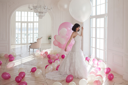 Young woman in wedding dress in luxury interior with a mass of pink and white balloons. Charming young bride brunette with short haircut in stylish Quinceanera dresses.