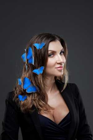 Beauty Fashion Model Girl surrounded by swarms of butterflies. Stock Photo