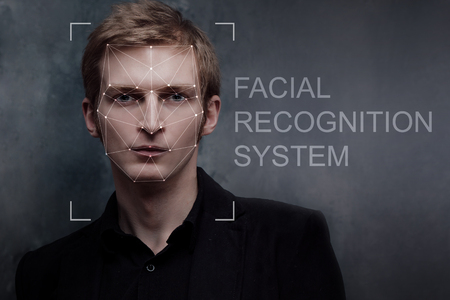 Facial recognition system, concept. Young man on the grey  background, face recognition