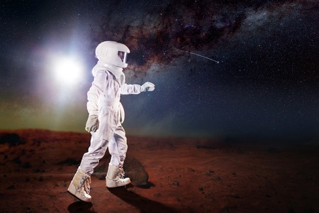 Futuristic astronaut on the planet, standing and stretches hand away Stock Photo
