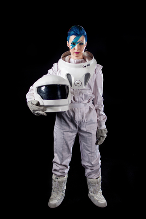 Astronaut on a black background, a young woman with face art in the space suit.
