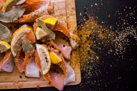 Sliced salmon steaks with lemon and spices. On a wooden Board. Healthy diet