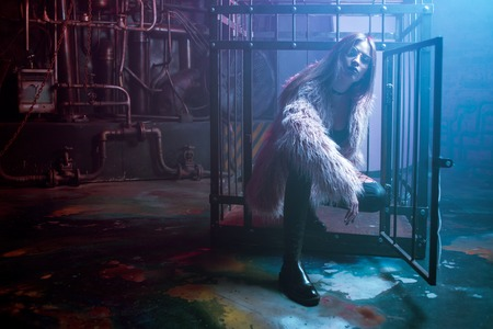 Young attractive woman with stylish clothes. Beautiful girl in a fluffy pink fur coat, cyberpunk background. Neon light