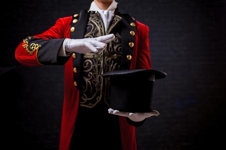 Illusionista mago, Primo piano della mano in guanti Il ragazzo con la canotta rossa e il cilindro. tiene il cappello tra le mani, agita le mani