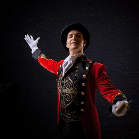 Forain. Jeune artiste masculin, présentateur ou acteur sur scène. Le gars dans la camisole rouge et le cylindre écartant les mains Banque d'images