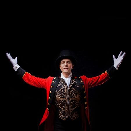 Forain. Jeune artiste masculin, présentateur ou acteur sur scène. Le gars dans la camisole rouge et le cylindre écartant les mains