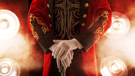 Forain. Pose, les mains reposent sur le bâton. Gants blancs et belle manche de son manteau, fumée sur fond de projecteur
