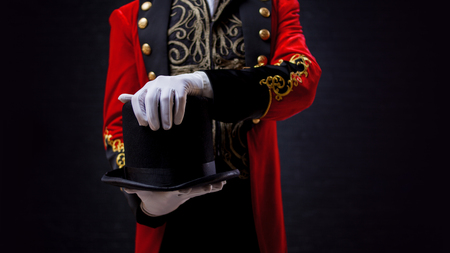 Magician. Close-up of hand in gloves The guy in the red camisole and the cylinder. Bright tailcoat, suit