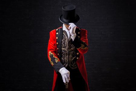 Forain. Jeune artiste masculin, présentateur ou acteur sur scène. Le gars dans la camisole rouge et le cylindre. Regardant vers le bas, la main sur le chapeau