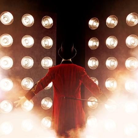 Showman. Junger männlicher Entertainer, Moderator oder Schauspieler auf der Bühne. Zurück, Arme zu den Seiten, Rauch auf dem Hintergrund des Scheinwerfers