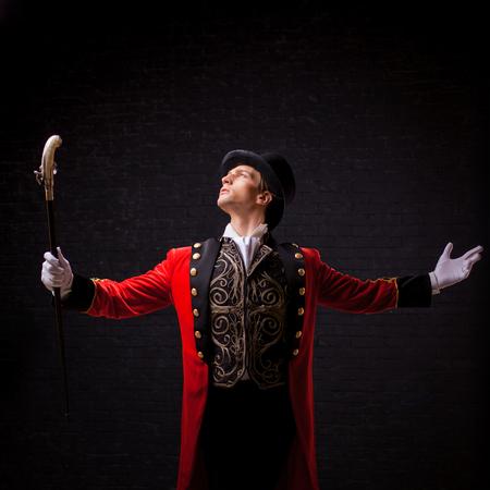 Showman. Junger männlicher Entertainer, Moderator oder Schauspieler auf der Bühne. Der Mann im roten Leibchen und der Zylinder breiteten die Hände aus Standard-Bild - 98840827