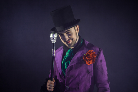 Showman. Young male entertainer, presenter or actor on stage. The guy in the purple camisole and the cylinder. Bright tailcoat, suit Banque d'images
