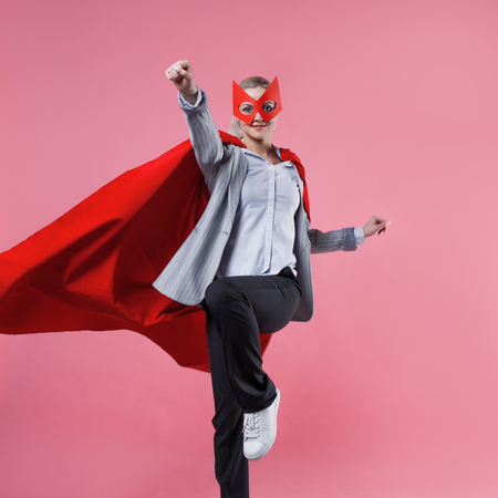 Young attractive woman superhero. Girl in a business suit and a mask with red cloak of hero. On a pink background. Jumps Stock Photo