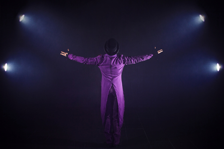 Young man in purple suit standing on the background of the spotlight. Showman spreading hands, show begins. Back view