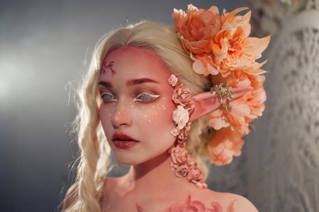 Young beautiful woman like the elf. Creative make-up and bodyart. Elvish ears, hairdo with flowers.