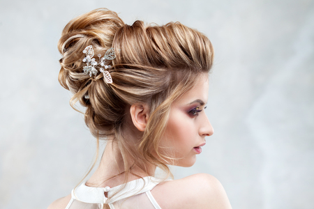 Young beautiful bride with an elegant high hairdo. Wedding hairstyle with the accessory in her hair. Close-up portrait on light background