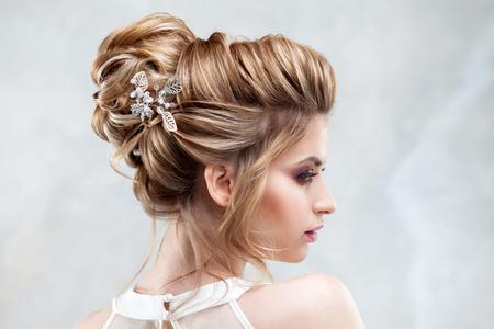 Jeune belle mariée avec une coiffure haute élégante. Coiffure de mariage avec l'accessoire dans ses cheveux. Portrait en gros plan sur fond clair Banque d'images