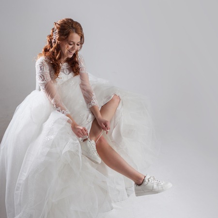 The girl in a magnificent wedding dress and white sneakers. Runaway bride. Studio, grey background Stock Photo