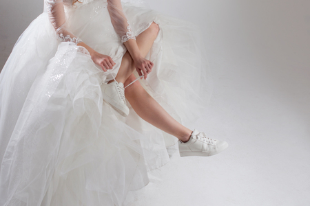 The girl in a magnificent wedding dress and white sneakers, legs close-up. Runaway bride