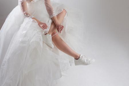 웅장한 웨딩 드레스와 흰색 운동화, 다리 클로즈업의 소녀. 달아난 신부