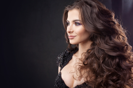 Portrait of a young attractive woman with gorgeous curly hair. Attractive brunette. Close up