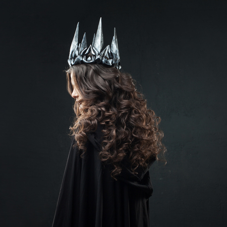 Portrait of a Gothic Princess. Beautiful young brunette woman in metal crown and black cloak. Mystical image Standard-Bild