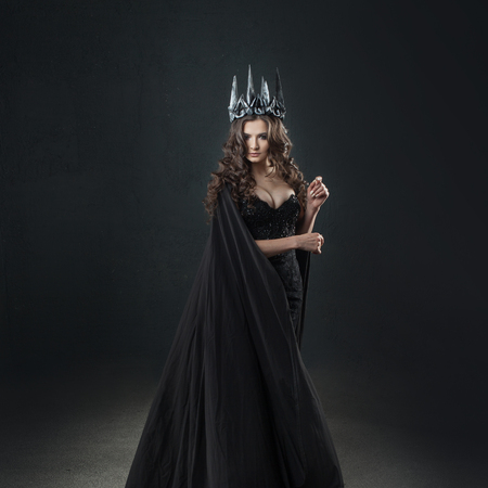 Portrait of a Gothic Princess. Beautiful young brunette woman in metal crown and black cloak. Mystical image Фото со стока