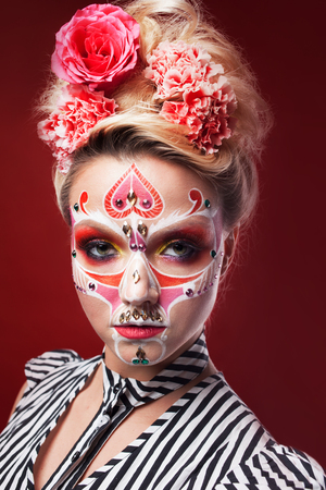 Young beautiful woman with skull makeup. Mexican day of the dead, art in the style of sugar skulls