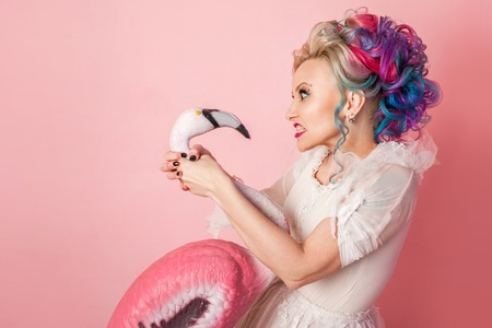 Stylish and beautiful woman with colored hair. Strangles a pink Flamingo figure. Pink background