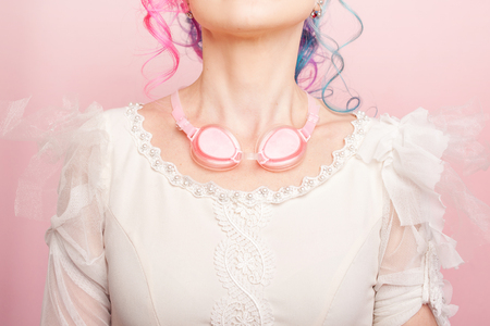 Trendy girl in white dress. Creative hair coloring with pink glasses on neck. The concept of naivety. Close up