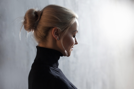Portrait of beautiful blonde woman. Calm and self-confidence. Beautiful adult girl in black turtleneck, gray background free space Stock Photo