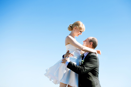 Newly-married couple. Groom and the bride, wedding walk. Young man and woman against the sky, free space on the left 版權商用圖片