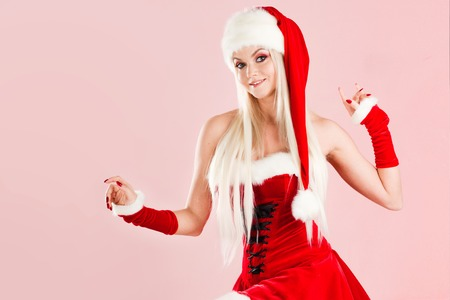 Charming and attractive blonde woman in a Santa suit. Christmas carnival, a beautiful girl in a snow maiden costume or Santas assistant Stock Photo