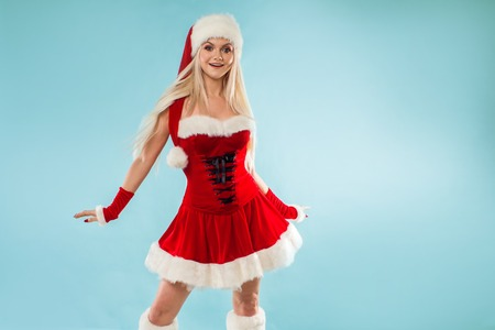 Charming and attractive blonde woman in a Santa suit. Christmas carnival, a beautiful girl in a snow maiden costume or Santa's assistant Stock Photo