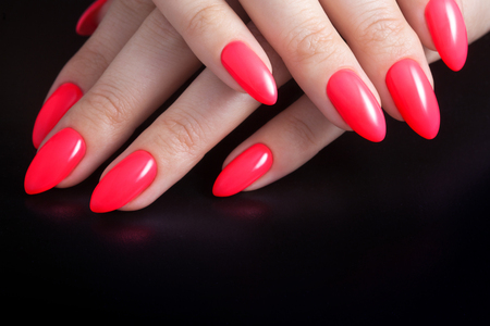 Women's hands with perfect red manicure. Nail Polish red coral color. Black background, close-up