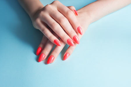 Womens hands with perfect red manicure. Nail Polish red coral color. blue background, close-up Stock Photo