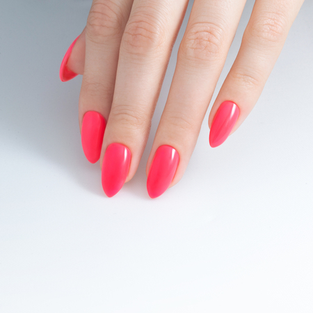 Paint your nails. Nail Polish, gel coating, red coral color. white background , close-up