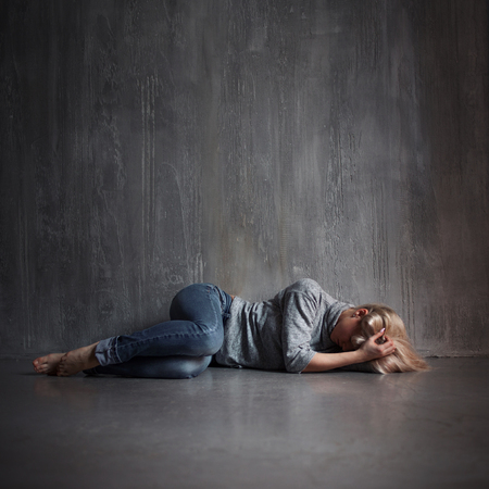 Depression. Young woman lying on the floor covering head with hands, concept of stress, copy space on the top