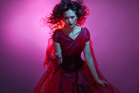 Gothic girl in red. Dancing young femme fatale. Neon light, Halloween party