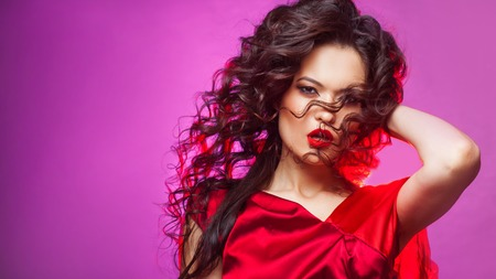 Portrait of an attractive brunette with lush styling and red lipstick. Young woman in red on purple background