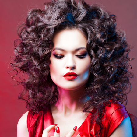 Big hair. Voluminous curls. Thick and voluminous hair, portrait of a beautiful young woman with red lipstick
