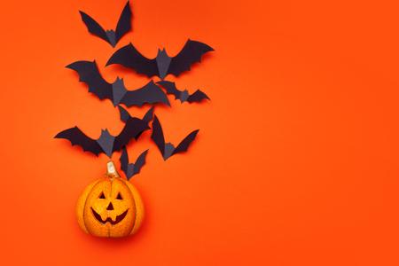 Halloween concept, swarm of bats on background of Halloween pumpkin lantern. bright orange background, copy space Stock Photo