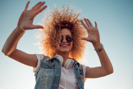 Charming curly blonde music lover gives fives.. Young woman with big headphones. outdoors portrait of a trendy girl 版權商用圖片