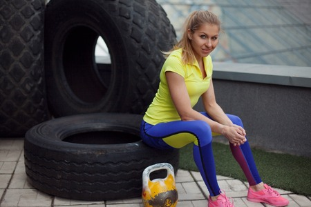 Athletics, after training with tyre. Smiling young female sportswoman sitting on a tire, ready to workout