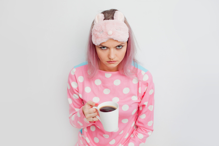 Unhappy girl slept badly. Portrait of grumpy woman in pink pyjamas. Blonde in a sleep mask, no sleep, insomnia.