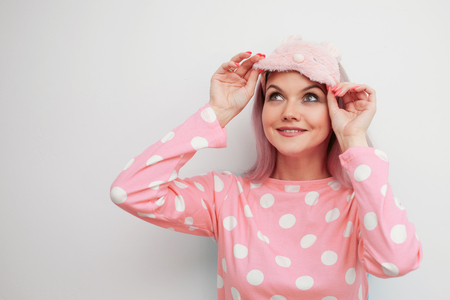 Beautiful young blonde in pink pajamas and a sleep mask. girl woke up in the morning, concept of cheerful beginning of day