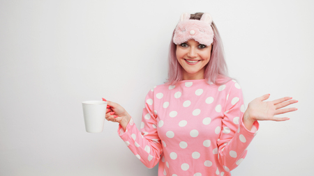 Happy young woman drink morning coffee. Beautiful girl in pink pajamas and mask for sleep