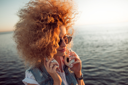 Trendy girl with large headphones and sunglasses on a city walk, close up. Portrait of a young charming blonde with lush curls, music lover on the sea background Banco de Imagens