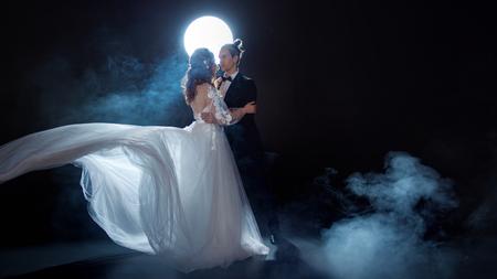Geheimnisvolles und romantisches Treffen, Braut und Bräutigam unter dem Mond. Umarmungen zusammen. Mann und Frau, Hochzeitskleid. Dunkler Hintergrund Standard-Bild